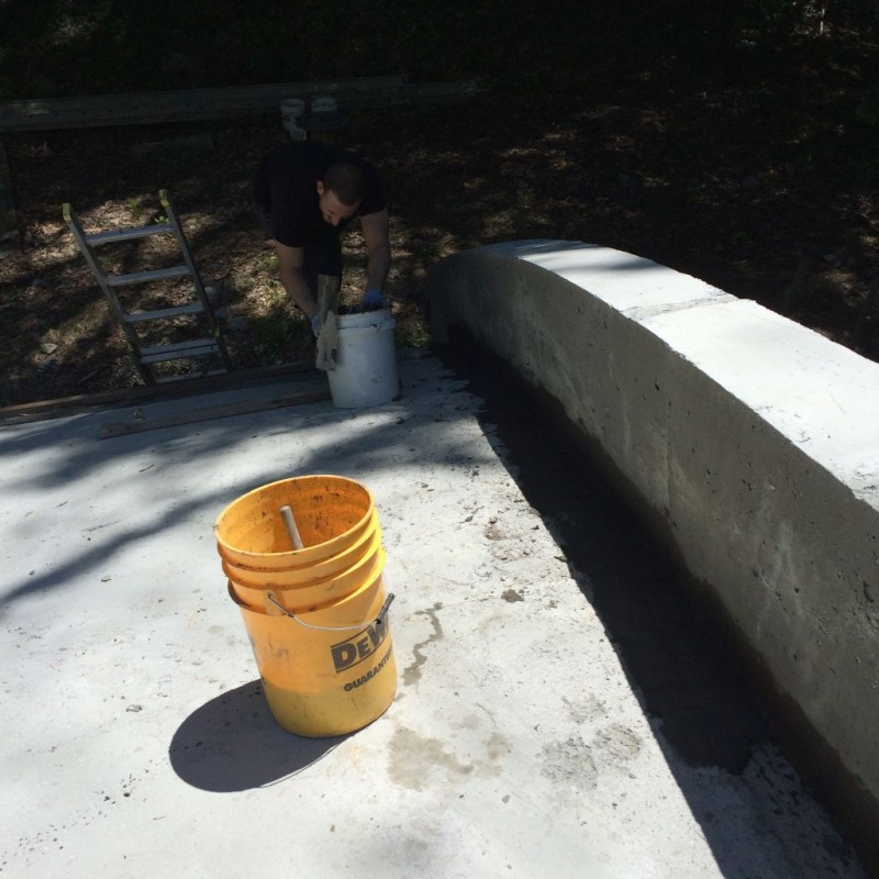 Jeff patching the retaining wall curb where the styrofoam is.