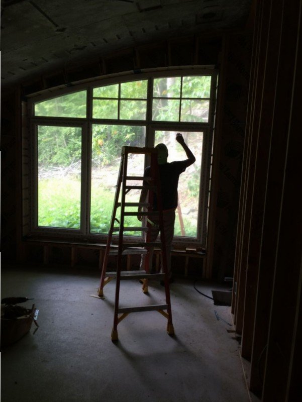 Peter stripping the protective coating off the window..