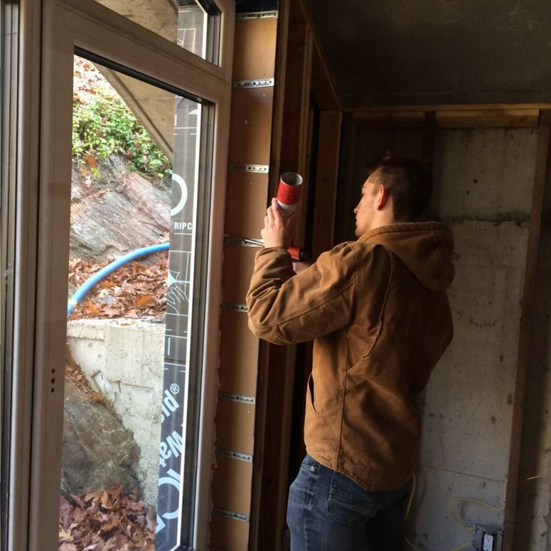 Terence spray foaming the area between the window and the framing.