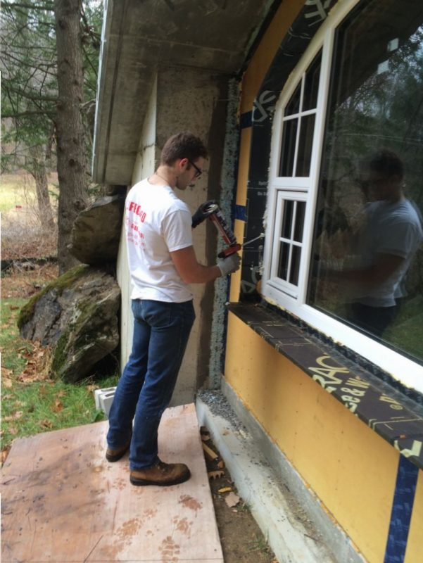 Jude finishing the spray foam around the windows.